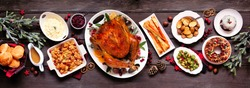 Traditional Christmas turkey dinner. Top view panoramic table scene on a dark wood banner background. Turkey, potatoes and sides, stuffing, fruit cake and plum pudding.
