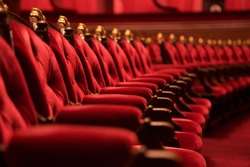 Traditional classically regal ornate rounded wood armed formal plush deep red velvet opera movie theater chairs in curved row with decorative gold molding in fancy carpeted venue