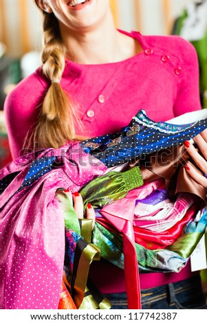 Traditional clothes - young woman is buying Tracht or dirndl in a shop, she has lots of dirndl in her arms