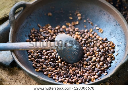 Traditional coffee beans roasting in metal basin with spoon, shallow depth of field