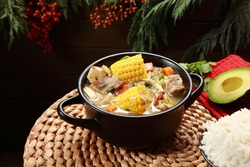Traditional Colombian Meat Stew Soup including Chicken Beef Maize Sweet Potato and topped with a savory sauce along with rice side dish. Sancocho de Costilla