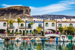 Traditional Colorful Buildings With Boats In Front And Mountain In The Background - Puerto de Mogan, Gran Canaria, Canary Islands, Spain