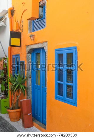 Traditional colorful house with blue windows on the street in Santorini, Fira, Greece. - stock photo