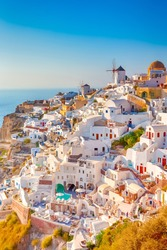 Traditional Colorful Houses and Windmills of Oia or Ia at Santorini Island at Noon. Vertical Image Orientation