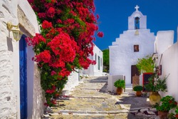 Traditional colorful mediterranean street with flowers and church, Amorgos, Cyclades, Greece, Europe