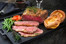 Traditional Commonwealth Sunday roast with sliced cold cuts roast beef with vegetable and Yorkshire pudding as closeup on a modern design cast iron tray
