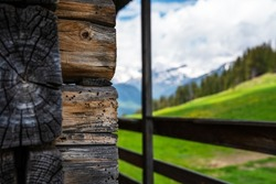 Traditional country house in Alps. Summer with a blue sky and green meadow. Wooden terrace with weathered wooden logs. Mountain summit house. Rent a house in the village concept.