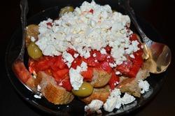 Traditional cretan salad Dakos (known as: koukouvagia, koukouvayia, kouloukopsomo) consisting of a slice of dried bread or barley rusk, crumbled feta or mizithra cheese, tomatoes, olives and oregano.