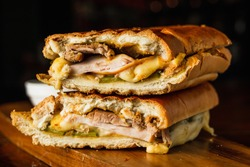 Traditional cuban sandwich with cheese, ham and fried pork, served on a wooden board