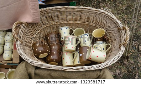traditional cute ceramic cups and mugs with colorful dots on pile in wooden baskets being sold at carnival festivities in Roznov city  at Wallachian museum in Moravia, Czech Republic, Central Europe