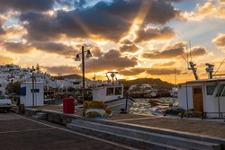 Traditional Cycladitic view with moored traditional fishing boats during an amazing sunset on the picturesque harbor of Naousa Paros, Greece.