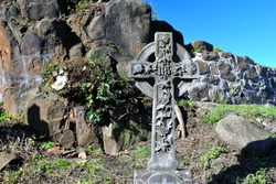 Traditional Decorated Stone Celtic Cross  seen against Rocky Background & Blue Sky