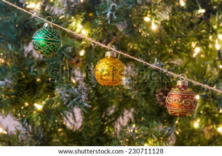 Traditional decorative Christmas balls hanging from rustic twine in front of Christmas tree