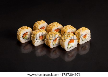 Traditional delicious fresh sushi roll set on a black background with reflection.  Sushi roll with rice, cream cheese, avocado, salmon, sesame. Philadelphia. Sushi menu. Japanese kitchen, restaurant.