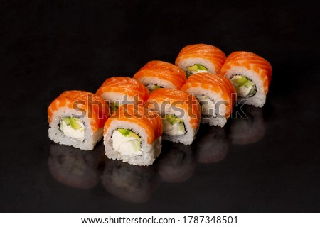 Traditional delicious fresh sushi roll set on a black background with reflection.  Sushi roll with rice, cream chees, red fish, salmon. Sushi menu. Japanese kitchen, restaurant. Seafood, asian food