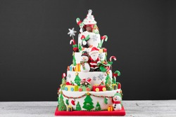 Traditional Delicious Iced Whole Christmas Cake with santa claus and snowman decoration on rustic white wood background with copy space.