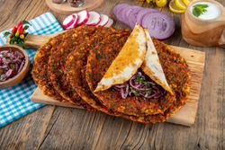 Traditional delicious Turkish foods; Lahmacun (Turkish pizza). Lahmacun traditional Turkish pizza and wraps with salad isolated on rustic wooden table.