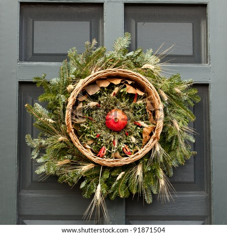 Traditional design of a christmas wreath attached to the front door of old house