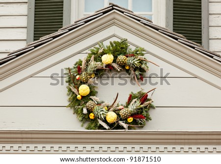 Traditional design of a christmas wreath attached to the front of old house
