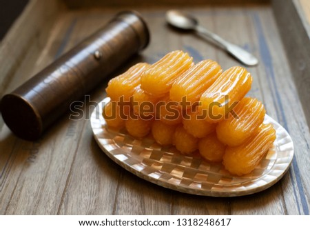 Traditional dessert called tulumba. Turkish cuisine. Balkan cuisine. Levantine cuisine. On a wooden background, served on a vintage oriental plate, in the background a vintage coffee grinder #1318248617
