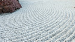 Traditional Details of Classical Japanese Zen Garden. Volcanic stones surrounded raked concentric lines gravel or sand. Symbolic imitation essence of nature in Japan. Gravel Rocks Garden. Meditation.