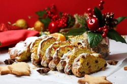 Traditional Deutsche  Cake Stolen Sliced With Cookies, Spices, Christmas Decoration On Red Background. Side View. Christmas Baking Concept.