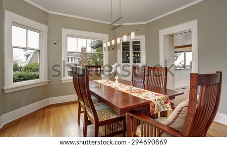 Traditional dinning room with hanging light fixture and windows.