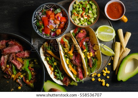 Shutterstock Traditional dish - Mexican tacos with ingredients meat and vegetables on the plate on a black wooden background, top view. Lots of space for text and design.
