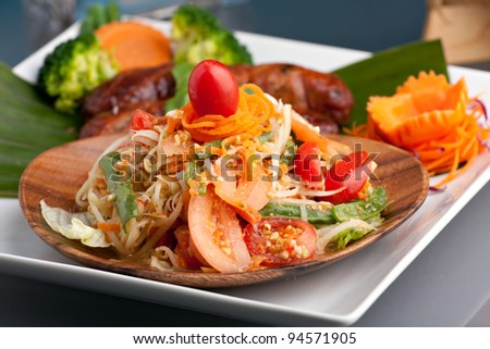 Traditional dish of freshly prepared Thai food.  Thai Sausage and som tum green papaya salad.