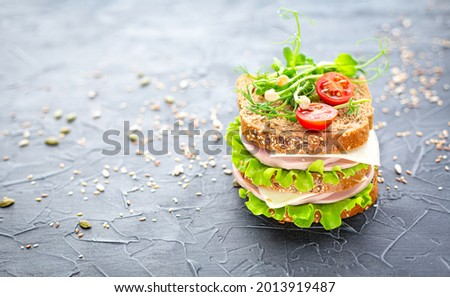 Traditional double sandwich of grain bread with sausage, cheese, herbs, cherry tomato and sesame seeds on a dark textured background. School lunch, fast food. Delicious sandwich for the cafe menu. Foto stock ©