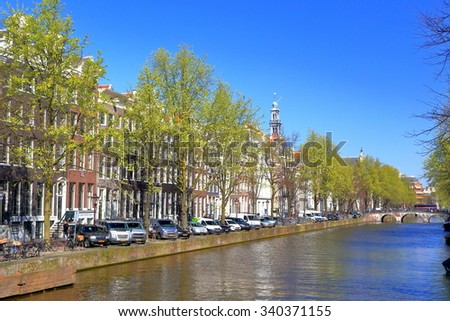 Traditional Dutch buildings along sunny canal in Amsterdam, Holland  #340371155