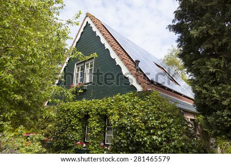 traditional dutch house with wooden front and solar panels in summer #281465579