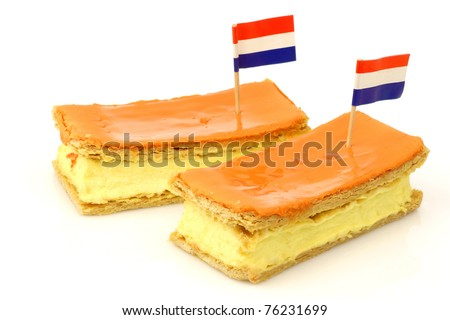 "Traditional Dutch pastry called ""tompouce"" with a Dutch flag toothpick especially produced for  Queens day on april 30th in Holland on a white background"