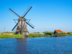 Traditional dutch windmill and small house with red roof surrounded by green grass near the canal with clear blue sky and blue water as background (Kinderdijk, South West of Rotterdam, Netherlands)