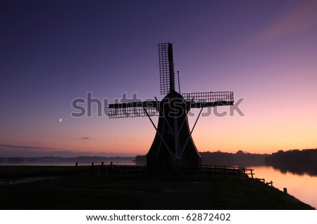 Traditional Dutch windmill at an autumn sunset at a lake, Groningen