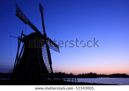 Traditional Dutch windmill at dusk, with a new moon in the sky.