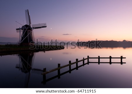 Traditional Dutch windmill at dusk, with the new moon and a star in the sky.