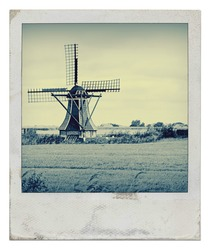 Traditional dutch windmill on the countryside in the netherlands edited with a vintage look