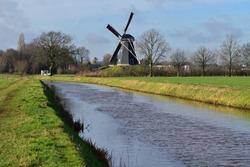 Traditional Dutch windmill overlooking a drainage kinderdijk under a blue winter sky