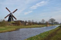 Traditional Dutch windmill sat beside a relaxing canal under a blue winter sky