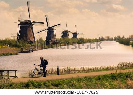 Traditional Dutch windmills and tourist by bike