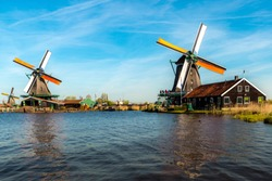Traditional dutch windmills located by the river Zaan, in Zaanse Schans, Netherlands. Landscape and culture travel, or historical building and sightseeing concept