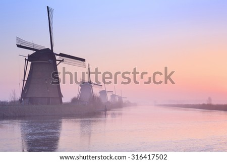 Stock Photo Traditional Dutch windmills on a cold morning at sunrise in winter, at the Kinderdijk in The Netherlands.