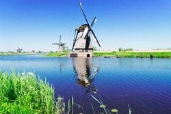 traditional dutch windmills with green grass and blue canal in Kinderdijk at summer day, Netherland