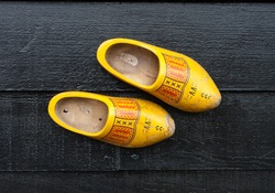 traditional dutch wooden shoes hanging at a wall