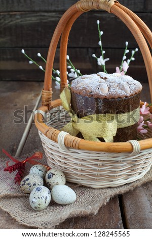 Traditional easter cake in the basket with Quail Eggs on the wooden table in rustic style, focus on the cake
