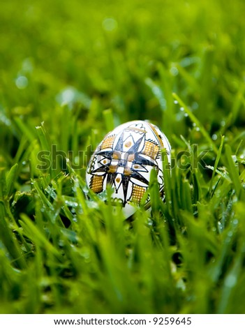 Traditional Easter Egg, painted with the symbol of the cross, on bright green grass covered with morning dew