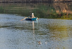 Traditional egyptian bedouin fisherman in rowing boat on river Nile fishing by riverbank