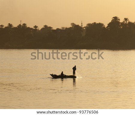 Traditional egyptian fishermen in a rowing boat on the Nile at sunset