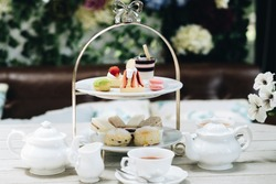 Traditional English afternoon tea: scones with clotted cream and jam, strawberries, with various sandwiches on the background